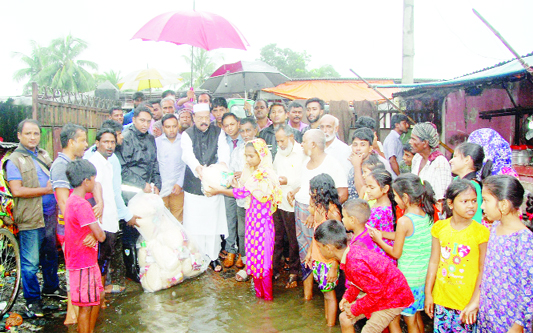 SYLHET:  President of Sylhet City Awami League and former mayor   Badar Uddin Ahmed Kamran distributing relief goods amoing the flood- hit people at  Taranton area  recently.