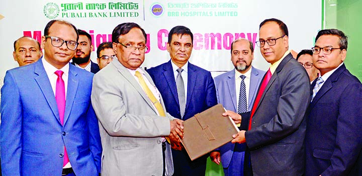 Md Abdul Halim Chowdhury, Managing Director of Pubali Bank Ltd and Major (Retd) AKM Mahbubul Hoque, Chief Executive Officer of BRB Hospitals Ltd, exchanging a Memorandum of Understanding (MoU) signing document at the Bank's head office in the city on Tuesday. Mohammad Ali, Deputy Managing Director of the bank was also present. Under the deal, all card holders and employees of bank will avail 10 to 20 percent discount while taking healthcare services from BRB Hospitals Ltd along with other facilities.
