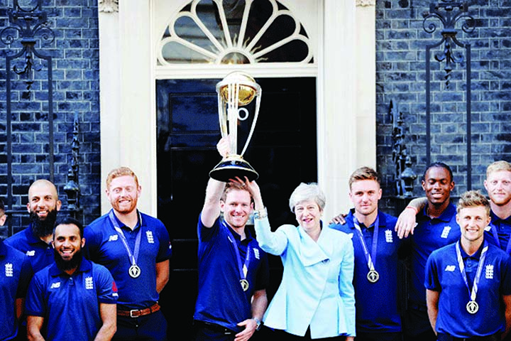 England Captain Eoin Morgan and his team-mates with British Prime Minister Theresa May and the World Cup trophy outside 10, Downing Street, the British PM's office and home in London on Monday.