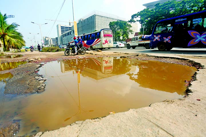 A vital portion of highway in Uttara near Armed Police Office is in dilapidated condition where big potholes and cracks following incessant rains for the last few days and works relating to metro-rail project, other development works. This photo was taken on Thursday.