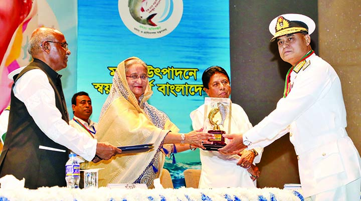 Prime Minister Sheikh Hasina handing over National Fishery Award-2019 to the Chief of Naval Staff Admiral Aurangzeb Chowdhury for his contribution for the development of country's fishery resources at a ceremony held in KIB auditorium in the city on Thursday.
