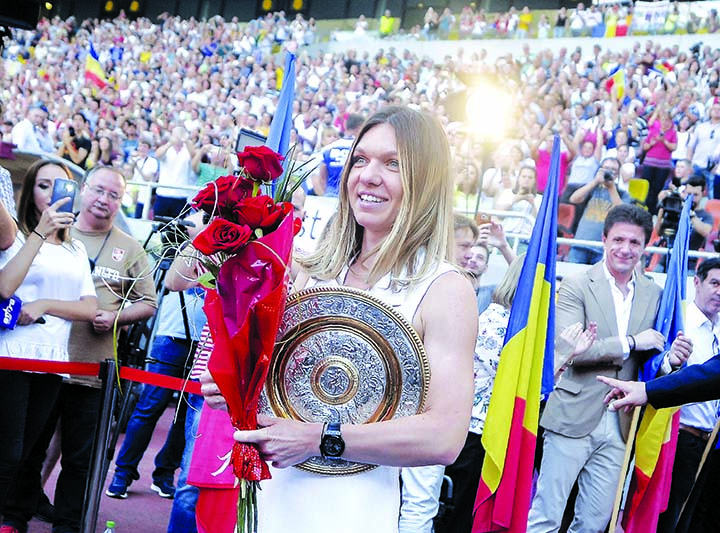 Romania's Simona Halep, winner of the 2019 Wimbledon Tennis Championships, arrives holding a replica of the tournament trophy, at an event, attended by thousands of fans, celebrating her success on the National Arena Stadium in Bucharest, Romania on Wednesday.