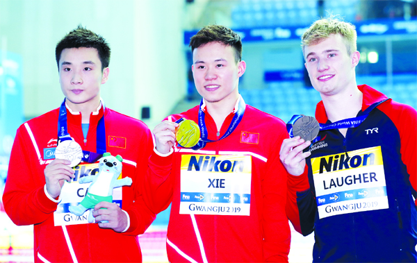 Gold medalist China's Xie Siyi (centre) stands with compatriot and silver medalist Cao Yuan and bronze medalist Britain's Jack Laugher (right) following the men's 3m springboard diving final at the World Swimming Championships in Gwangju, South Korea on Thursday.