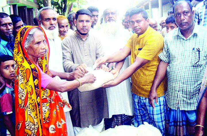 SAGHATA (Gaibandha):  Businessman  Alhaj Abdul Goni Bablu distributing relief goods among the flood- hit people at Bhangarpara Village  on Sunday.
