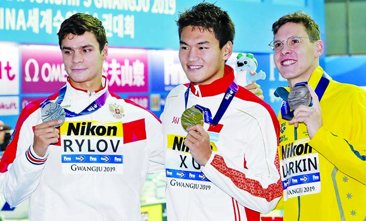 Gold medalist China's Xu Jiayu (centre) stands with silver medalist Russia's Evgeny Rylov (left) and bronze medalist Australia's Mitchell Larkin following the men's 100m backstroke final at the World Swimming Championships in Gwangju, South Korea on Tuesday.