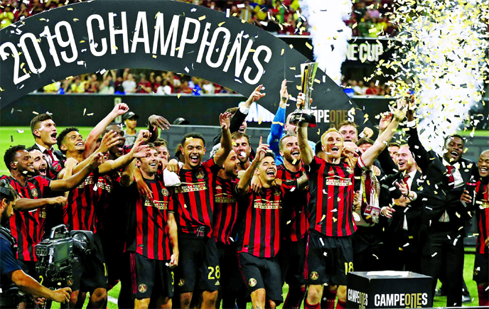 Atlanta United captain Jeff Larentowicz hoists the trophy for the team celebrating a 3-2 victory over Club America to win the Campeones Cup soccer match in Atlanta on Wednesday.
