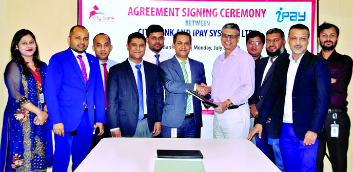 Md Mustafizur Rahman Ujjal, Head of ADC of City Bank and Zakaria Swapan, CEO of iPay Systems Ltd, exchanging an agreement signing document at the bank's corporate office in the city recently. Masudul Haque Bhuiyan, Head of Cards of the Bank and Raihan Faiz Osmani, Head of Merchants of iPay, among others, were present. Under the deal, customers of the Bank will be entitled to get the benefit of transferring money from their account to any of their personal iPay wallet using Citytouch.