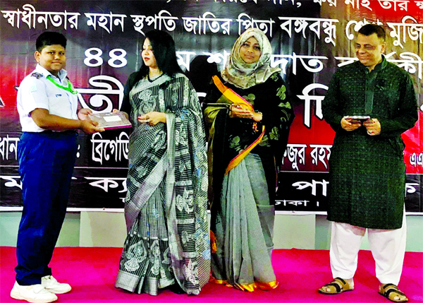 Birg Gen Mostafizur Rahman  and his wife handing over prize to Abdullah Mahmud, a student of class four for securing first place in Hammd Naath competition organised at the city's Adamjee Cantonment School on the occasion of the 44th martyrdom anniversary of Bangabandhu Sheikh Mujibur Rahman on Friday.