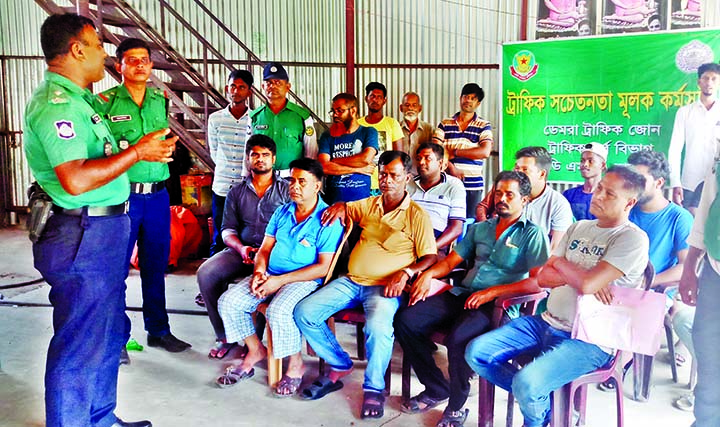 Traffic Inspector Biplab Bhowmik speaking at a traffic awareness programme held in the city's Kazla, Demra on Monday. Asmot Ali, member of Dhaka Tarabo Transport Owners Association and Mahbubur Rahman, owner of Srabon Paribahan, among others, were present on the occasion.