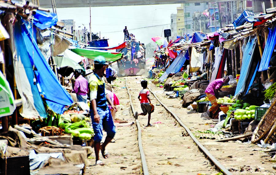 A train runs slowly as a vegetable market set up in close proximity of the railway track at Jurain in the capital despite restrictions to build structures within 50 yards of railway tracks. This photo was taken on Monday.