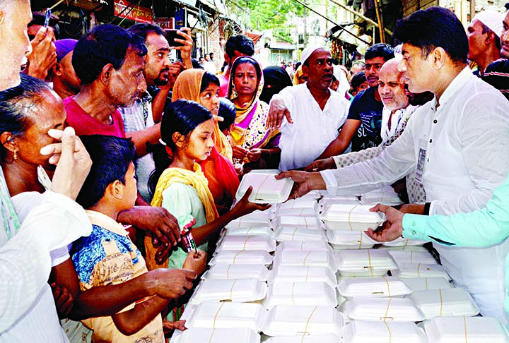 Councillor of 26 No. Ward of DSCC Hasibur Rahman Manik distributing food among the destitute organised on the occasion of National Mourning Day in the city