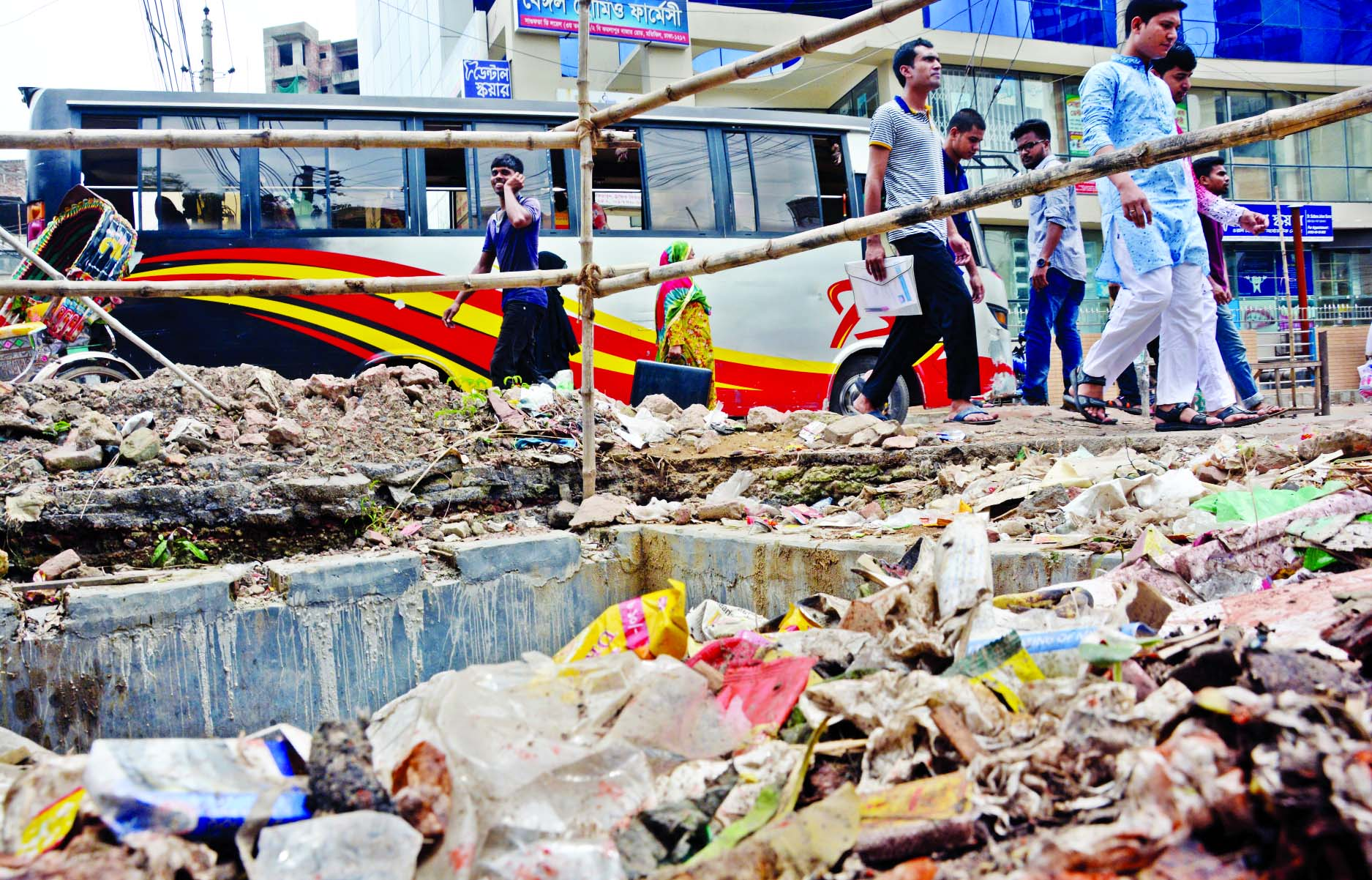 Pile of brickbats and soil in the capital's Toyenbee Circular Road in Motijheel beside the dug-up spots where the City Corporation is laying underground pipes to mitigate the water logging, causing miseries to the pedestrians in this rainy season. The photo was taken on Friday.