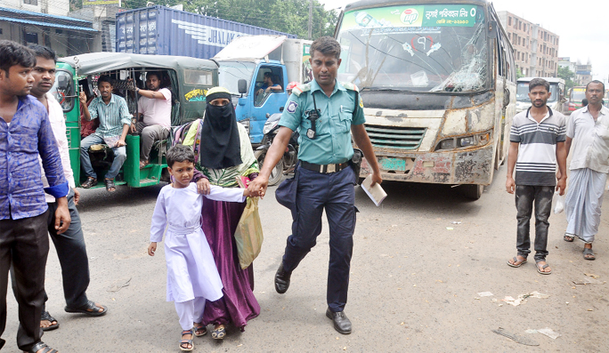 Lack of Zebra- crossing and foot over bridge, passengers taking help from a traffic  sergeant at  A K Khan Point yesterday.