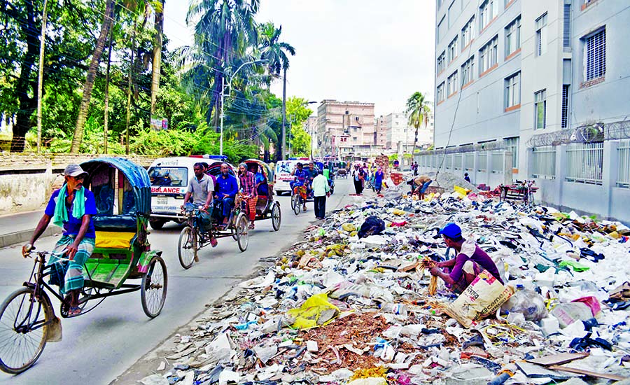 Waste and garbage dumped on many city streets still remain unattended turning the city into breeding grounds of mosquitoes. This photo was taken from near the entrance of Sheikh Hasina National Burn and Plastic Surgery Institute in Dhaka on Monday.