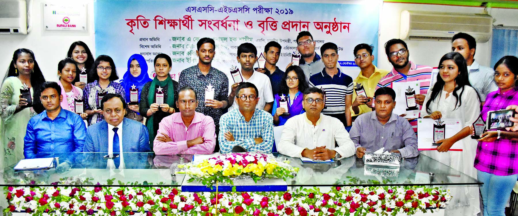 Deputy Minister for Water Resources AKM Enamul Haque Shamim poses for a photo session with the wards of DRU members who received scholarships for their brilliant results in the last SSC and HSC examinations in DRU auditorium on Tuesday.