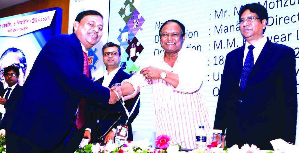 Mofizul Islam, Managing Director of A M Knitwear Limited, receiving the CIP card from Commerce Minister Tipu Munshi at a function held at a hotel in the city on Wednesday. Former Commerce Minister Tofail Ahmed and senior officials were also present.
