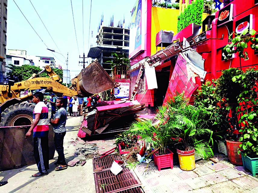 A DSCC bulldozer knocks down structures set up at Shahjahanpur Railway Colony in city on Sunday.