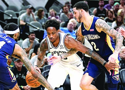 San Antonio Spurs' DeMar DeRozan( center) drives between New Orleans Pelicans' Brandon Ingram( left) and Lonzo Ball during the second half of an NBA preseason basketball game in San Antonio on Sunday.