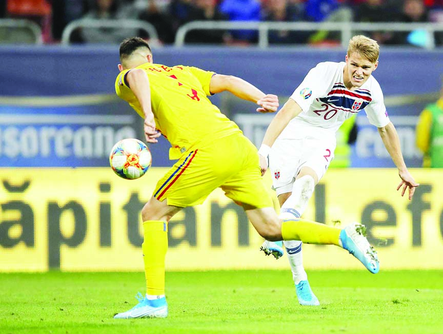 Romania's Ionut Nedelcearu (left) tries to block a shot from Norway's Martin Odegaard during the Euro 2020 group      F qualifying soccer match between Romania and Norway on the National Arena stadium in Bucharest, Romania           on Tuesday.