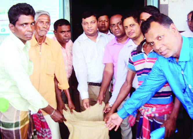 SAGHATA (Gaibandha): Mohiuddin Jahangir, UNO, Saghta Upazila distributing VGF rice  among the  fishermen to pass Hilsa ban period on Tuesday.
