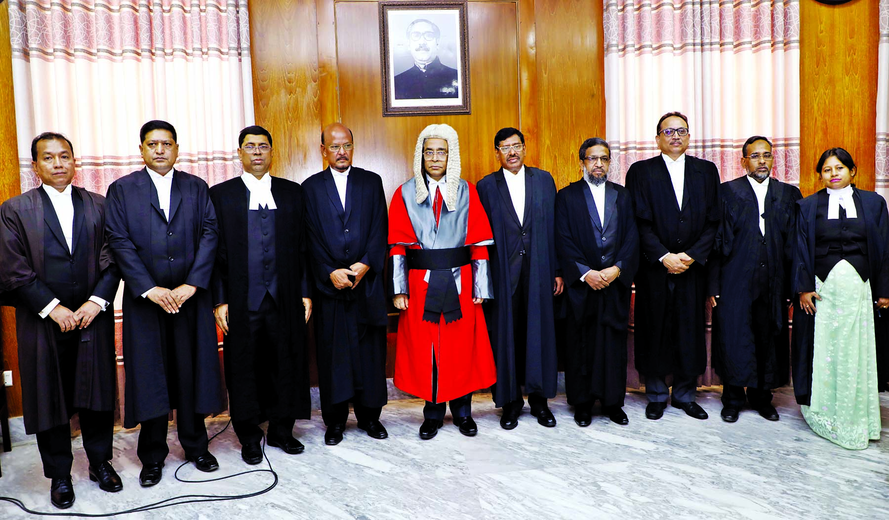 Chief Justice Syed Mahmud Hossain poses for a photo session with the newly appointed nine Additional Judges of the High Court after administering oath at the Judges Lounge of the Supreme Court on Monday.
