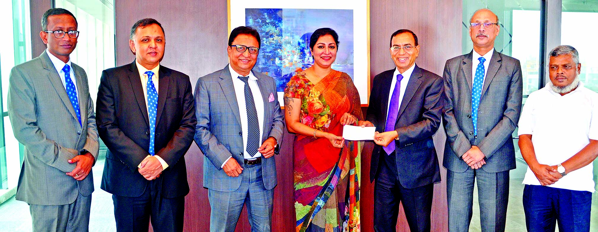 M. Shahidul Islam, Managing Director of Shahjalal Islami Bank Limited, handing over a cheque to Sajida Rahman Danny, President of Parents Forum for Differently Able (PFDA), at the bank's head office in the city on Tuesday. PFDA is mainly a non-government organization, working for eradicating Autism, Cerebral Palsy Down syndrome as well as intellectual & Neurological Disabilities from the Country. Top officials from both the sides were also present.