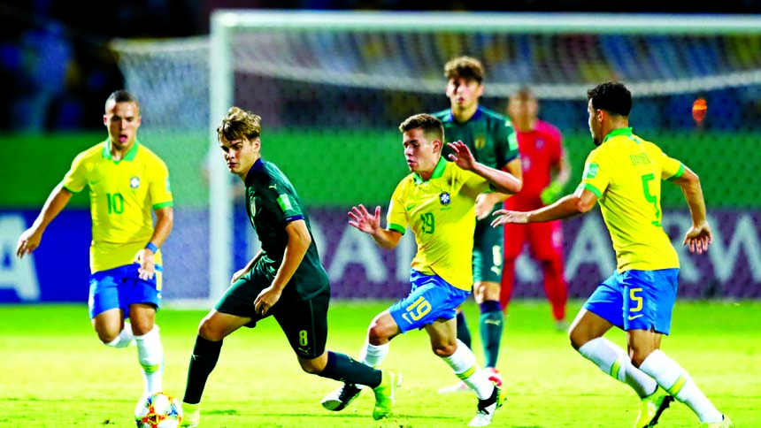 Michael Brentan (front) of Italy looks to break past Pedro Lucas (center) of Brazil and Daniel Cabral (right) of Brazil during the FIFA U-17 World Cup quarter-final match between Italy and Brazil at the Olympic Stadium Goiania in Goiania, Brazil on Monday.