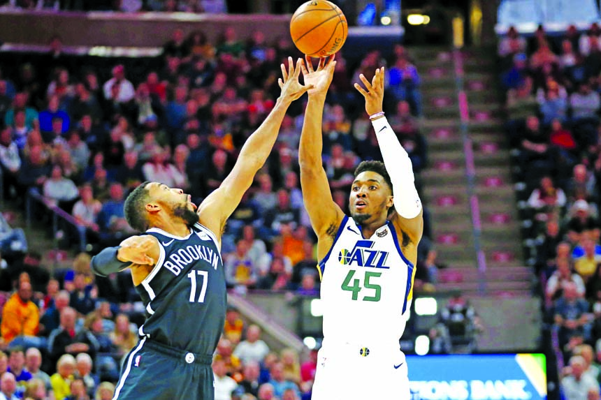 Utah Jazz guard Donovan Mitchell (45) shoots as Brooklyn Nets guard Garrett Temple (17) defends in the first half during an NBA basketball game in Salt Lake City on Tuesday.