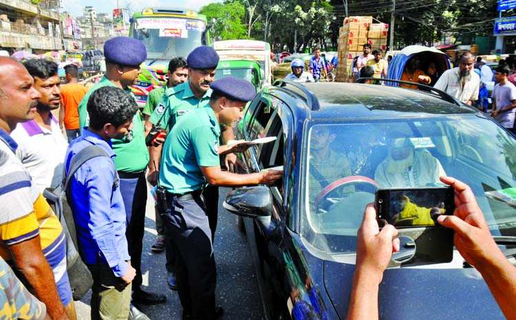 Officials of Lalbagh Traffic Zone distributing leaflets among the drivers and transport workers at Nayabazar in Dhaka on Wednesday as part of its public awareness campaign on the new Road Transport Act.