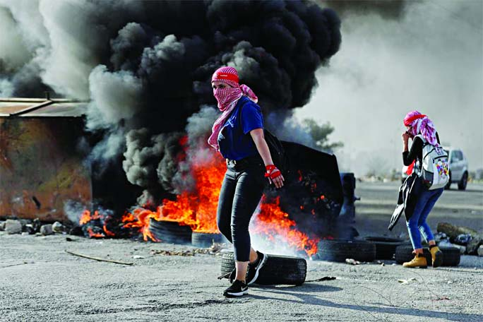A female Palestinian demonstrator is seen in front of burning tires during an anti-Israel protest near the Jewish settlement of Beit El in the Israeli-occupied West Bank on Saturday.