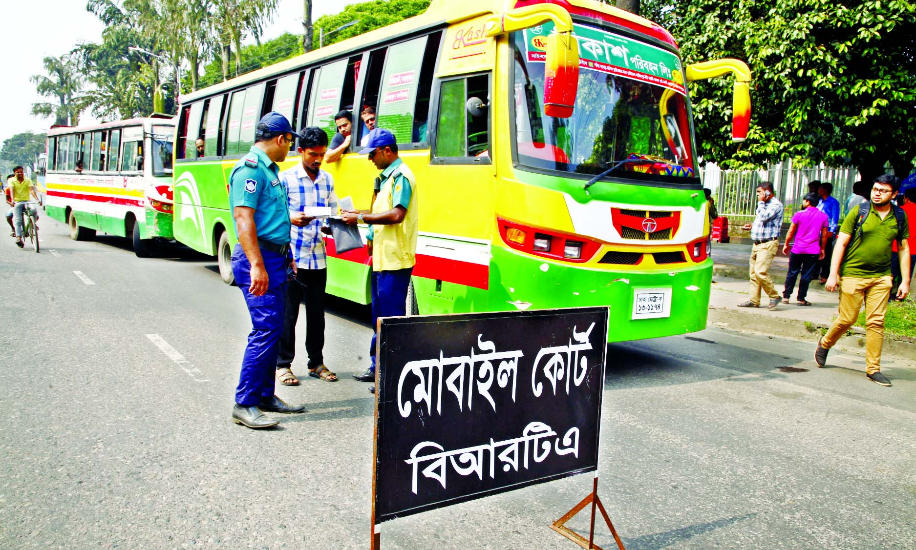 A traffic sergeant verifying documents from a bus driver during a mobile court of Bangladesh Road Transport Authority (BRTA) operated at Manik Mia Avenue in the capital on Monday.
