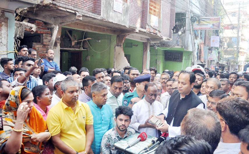 Deputy Education Minister Mohibul Hasan Chowdhury Nowfel MP distributing money yesterday among the family members of gas line explosion at Patharghata.