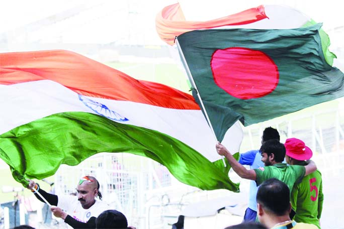 Indian and Bangladeshi cricket supporters cheer for their teams with their national flags ahead of their second cricket Test match between India and Bangladesh, in Kolkata, India on Thursday. The second and final game in the series is scheduled to be played in Kolkata starting today.