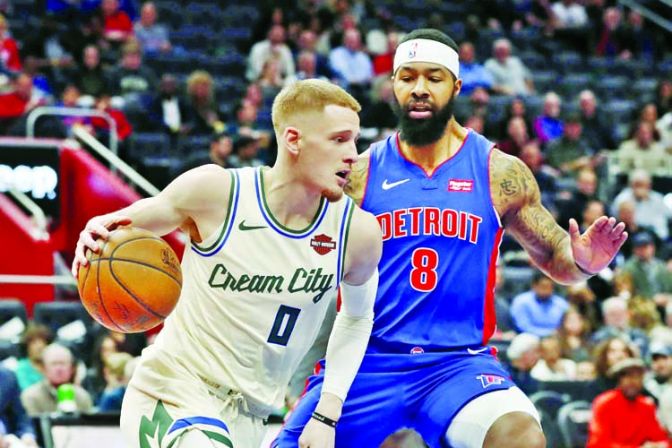 Milwaukee Bucks guard Donte DiVincenzo (0) drives around Detroit Pistons forward Markieff Morris (8) during the first half of an NBA basketball game on Wednesday.