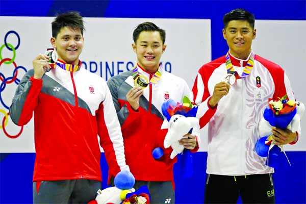 Gold medalist Singapore's Tzen Wei Teong (center) poses with silver medalist Singapore's Joseph Schooling (left) and bronze medalist Indonesia Glenn Sutanto (right) during awarding ceremonies for the men's 50m butterfly final during swimming competition at the 30th Southeast Asian Games in New Clark City, Tarlac province, Northern Philippines on Thursday.