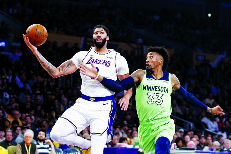Los Angeles Lakers' Anthony Davis (3) drives to basket while defended by Minnesota Timberwolves' Robert Covington (33) during the first half of an NBA basketball game in Los Angeles on Sunday.