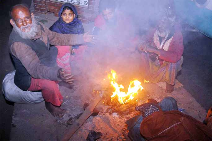 Poor people at Chattogram Old Rail Station warming themselves by burning straws  yesterday.