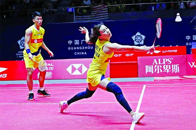 Malaysia's Goh Liu Hui  (right) hits a return shot against Thailand's Sapsiree Taerattanachai and Dechapol Puavaranukroh during the mixed doubles in the World Tour Finals at Guangzhou in south China's Guangdong province on Thursday.