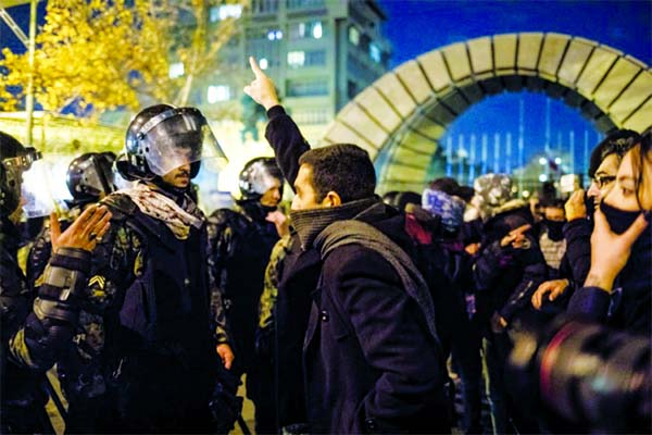 A man confronts riot police during a demonstration outside Tehran's Amir Kabir University after Iran admitted to having shot down a Ukrainian passenger jet by mistake.