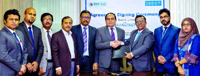 M. Fakhrul Alam, Managing Director of ONE Bank Limited and Mohammad Khairuzzaman, Country Director of Trans-Fast Remittance Bangladesh, exchanging document after signing an agreement at the banks head office in the city recently for paying out Bangladesh bound foreign remittance. Senior officials from both organizations were also present.
