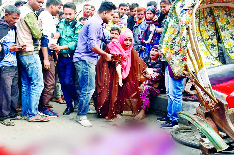 A girl was killed after a covered-van hit a rickshaw at Hatkhola Road in Dhaka on Thursday. Photo shows that relatives wailing as they mourn for the victim at the accident spot.