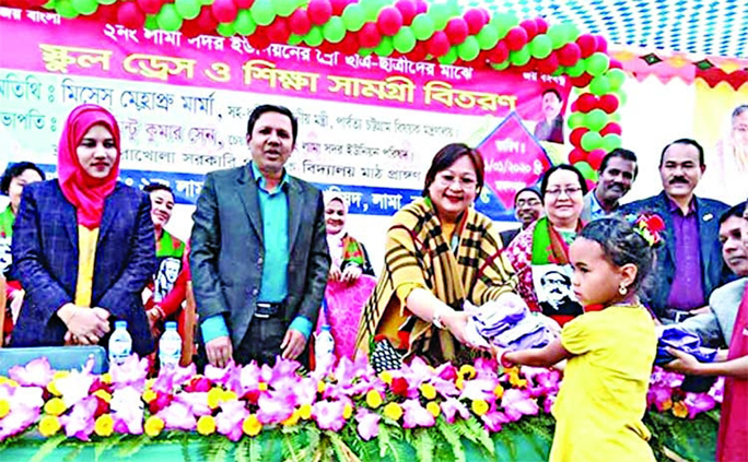 Hla May Prue Marma, wife of Chittagong Hill Tracts Affairs Minister Bir Bahadur  distributing educational  materials  among students in Bandarban  as  Chief Guest at a function in Merakhola Govt Primary School field on Wednesday noon.