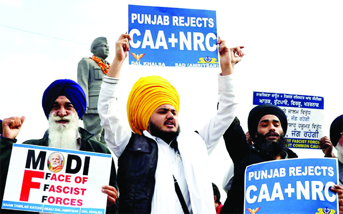 Demonstrator shout slogans as they display placards during a protest against a new citizenship law, in Amritsar, India on Saturday.