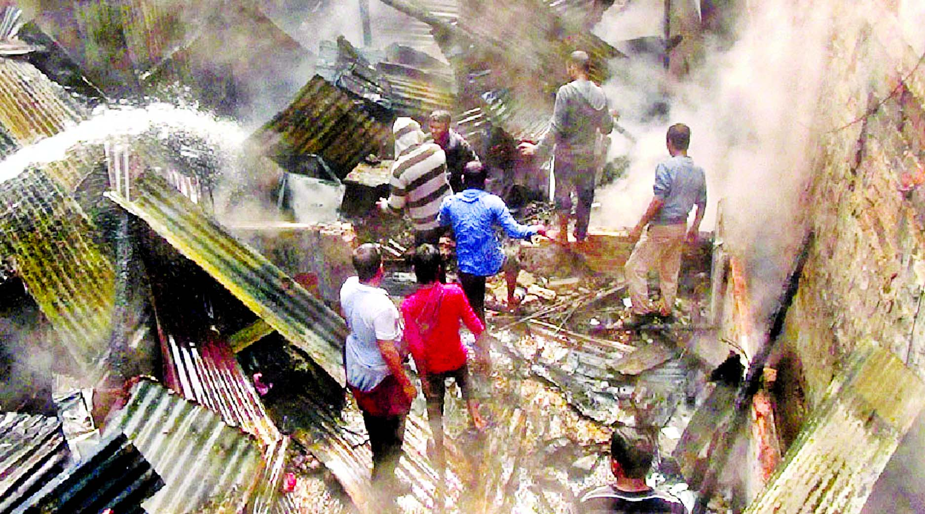 Firefighters and locals try to extinguish fire that broke out at a two-storey building in Moulvibazar, Sylhet on Tuesday.