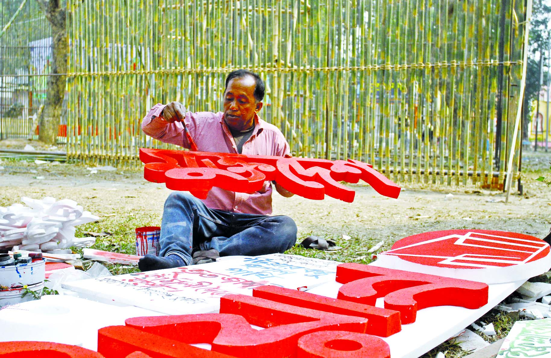 A man paints sign of a stall at the capital's Suhrawardy Udyan on Tuesday, as part of the preparations for the month-long Amar Ekushey Boi Mela to be opened on February 2.