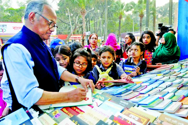 Eminent writer Emdadul Haque Milon giving autograph to children at the Ekushey Book Fair in the city's Suhrawardy Udyan on Tuesday.