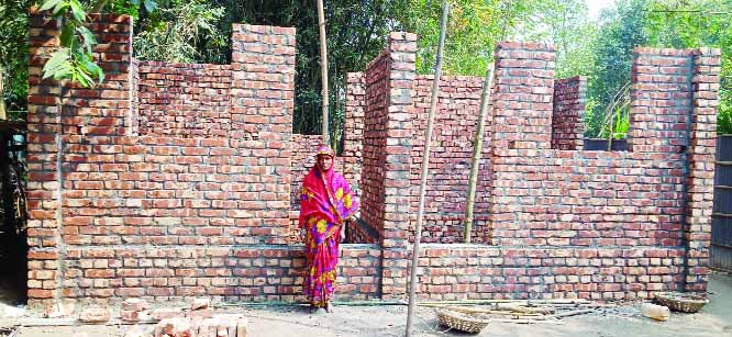KISHOREGANJ (Nilphamari): Jannati Begum at Masterpara Village in Putimari Union of Nilphamari Upazila  standing beside  her  house given by Rural Infrastructure Development Project  in 2019- 2020 fiscal year recently.