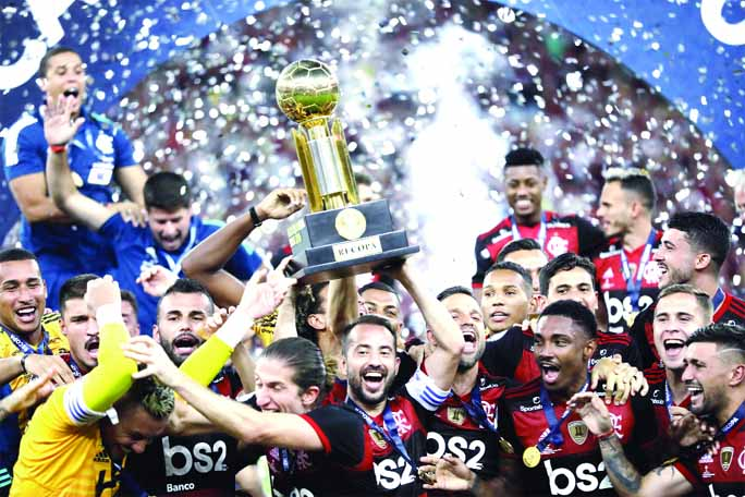 Players of Brazil's Flamengo celebrate with the trophy after defeating Ecuador's Independiente del Valle 3-0 in the final match of the Recopa at the Maracana stadium in Rio de Janeiro of Brazil on Wednesday.