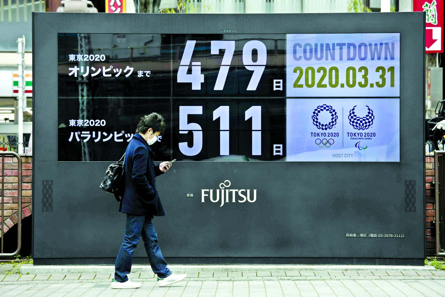 A man walks past a countdown display for the Tokyo 2020 Olympics and Paralympics in Tokyo on Tuesday. The countdown clock is ticking again for the Tokyo Olympics. They will be July 23 to Aug. 8, 2021. The clock read 479 days to go. This seems light years away, but also small and insignificant compared to the worldwide fallout from the coronavirus.