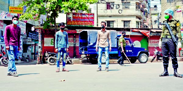 Law-enforcers awarding punishment to someone keeping them in standing position for roaming on the streets unnecessarily.  The snap was taken from the city's Dholaikhal Natun Rasta Intersection on Wednesday.